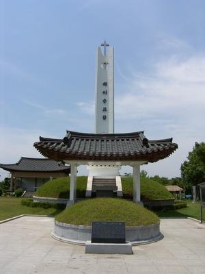 해미 성지의 무명 생매장 순교자들의 묘와 순교탑. 그 뒤로 야외제대가 있다.